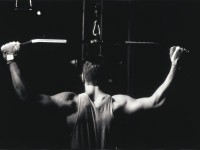 rear-view-of-a-young-man-exercise-on-a-lateral-pull-down-weight-machine